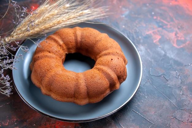Vista ravvicinata laterale una torta un piatto di torta accanto ai rami degli alberi e alle spighe di grano