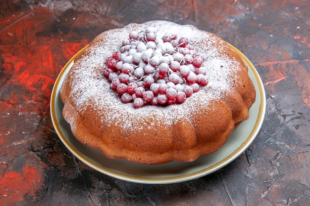 Vista ravvicinata laterale una torta un piatto di una torta con frutti di bosco e zucchero a velo