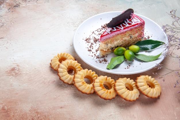 Vista ravvicinata laterale una torta sei biscotti accanto al piatto di una torta appetitosa