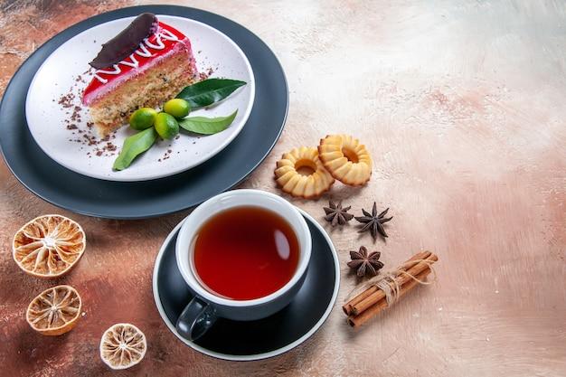 Vista ravvicinata laterale una torta anice stellato biscotti cannella una tazza di tè una torta
