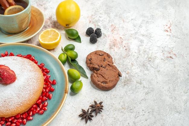 Боковой вид крупным планом торт с чашкой чая, торт из клубники чашка чая с лимоном, шоколадное печенье, звездчатый анис на столе