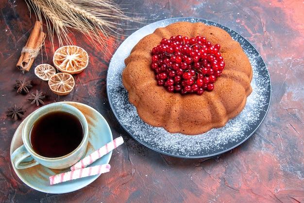Vista ravvicinata laterale torta con frutti di bosco torta con ribes rosso una tazza di tè con dolci limone e cannella