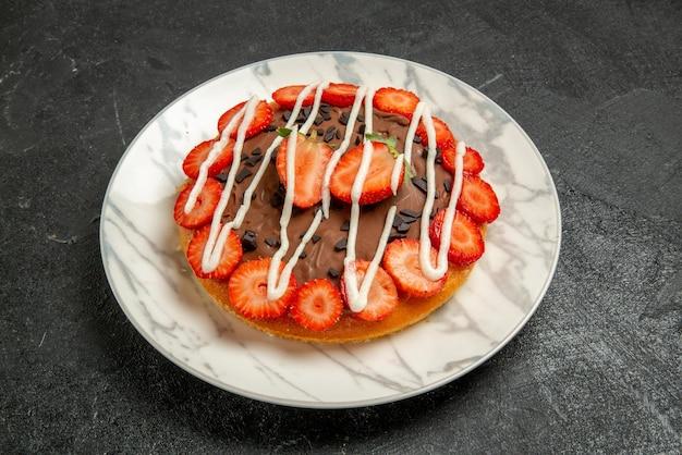 어두운 테이블 중앙에 초콜릿과 딸기가 있는 식욕을 돋우는 케이크의 초콜릿 접시가 있는 측면 클로즈업 보기 케이크