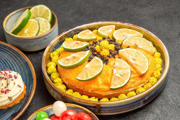 Боковой вид крупным планом торт с лаймами тарелку торта с лаймами рядом с миской конфет и ломтиками лайма и кекс на синем блюдце на столе