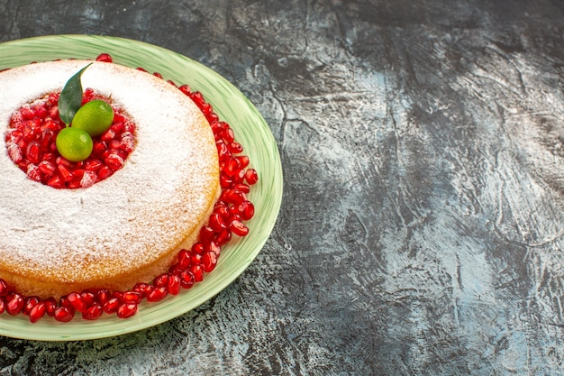 Side close-up view cake with pomegranate an appetizing cake with citrus fruits and pomegranate