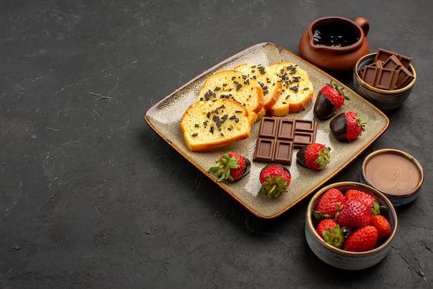 Vista ravvicinata laterale torta con fragole appetitosa torta con fragole ricoperte di cioccolato e ciotole di crema al cioccolato fragola e cioccolato sul lato destro del tavolo