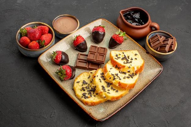 Vista ravvicinata laterale torta con fragole crema al cioccolato fragola e cioccolato in ciotole marroni e piatto di torta con fragole ricoperte di cioccolato su sfondo nero
