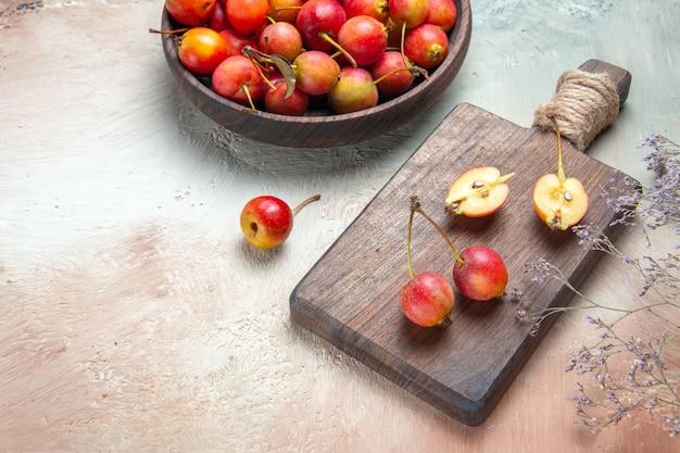 Вид сбоку крупным планом вишни чаша ягод вишни на ветке дерева доски