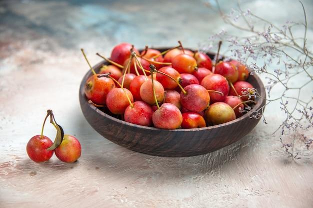 Вид сбоку крупным планом вишни вишни в деревянной миске рядом с ветвями дерева