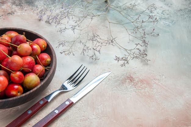 Вид сбоку крупным планом вишня вилка нож желто красная вишня в миске ветки деревьев
