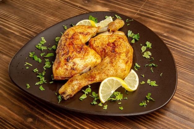 어두운 배경에 레몬과 허브를 곁들인 닭 다리의 측면 클로즈업 보기 닭고기와 허브 접시