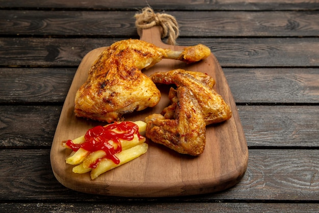 Боковой вид сбоку курица и специи куриные крылышки и ножка с картофелем фри и кетчупом на разделочной доске в центре темного стола