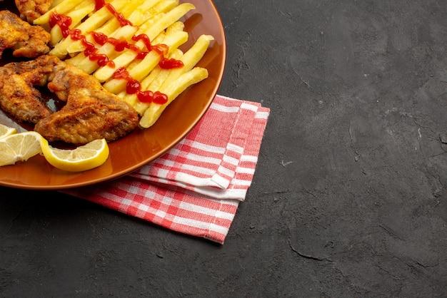 サイドクローズアップビューチキンフライドポテトのチェッカーテーブルクロスオレンジプレートの食欲をそそるフライドポテトチキンウィングケチャップとレモンの暗いテーブルの左側