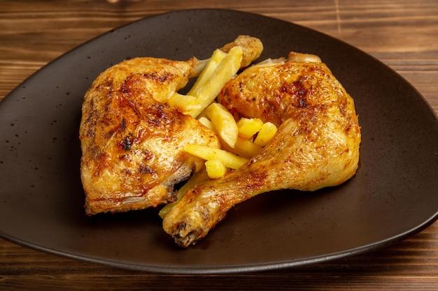 Vista ravvicinata laterale di cosce di pollo piatto di cosce di pollo e patatine fritte al centro del tavolo
