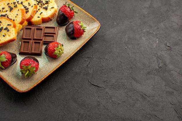 テーブルの左側にチョコレートで覆われたイチゴとケーキの側面のクローズアップビューチョコレートとケーキの正方形の灰色のプレート