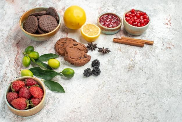 側面のクローズアップビューチョコレートクッキーチョコレートクッキーイチゴのボウル柑橘系の果物シナモンスティックテーブルに