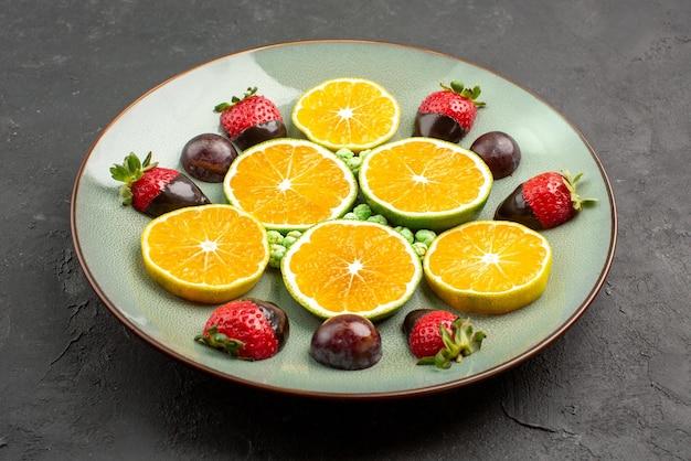 側面のクローズアップビューチョコレートで覆われた果物チョコレートで覆われたイチゴ緑のキャンディーと黒いテーブルの中央に食欲をそそるみじん切りオレンジ