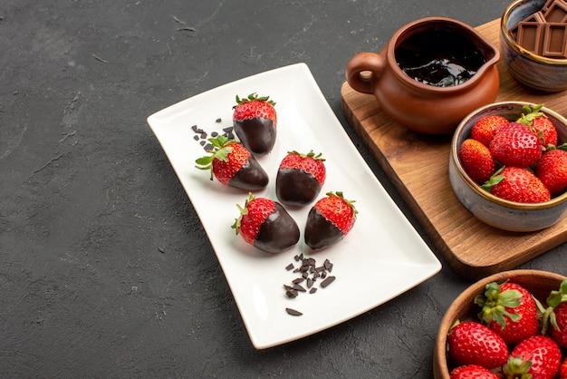 側面の拡大図チョコレートで覆われたイチゴのプレートチョコレートで覆われたイチゴのバーのチョコレートボウルのイチゴとキッチンボードとチョコレートクリームとイチゴ