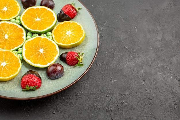 측면 클로즈업 보기 초콜릿으로 덮인 딸기 녹색 사탕은 검은색 테이블 왼쪽에 있는 접시에 오렌지와 초콜릿으로 덮인 딸기를 잘게 썬 것입니다.