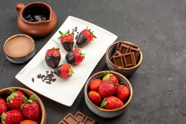 어두운 테이블에 초콜릿 덮인 딸기의 그릇 흰색 접시에 빨간 딸기 초콜릿 크림 그릇에 측면 클로즈업 보기 초콜릿