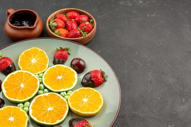 측면 클로즈업 보기 초콜릿 소스와 과일 녹색 사탕 초콜릿으로 덮인 딸기 다진 오렌지는 흰색 접시에, 초콜릿 소스와 딸기는 탁자 위의 그릇에 있습니다.