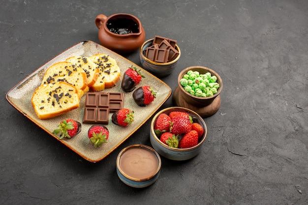 側面の拡大図チョコレートイチゴケーキチョコレートイチゴ緑のキャンディーとボウルのチョコレートクリーム食欲をそそるケーキと暗いテーブルの上のイチゴ