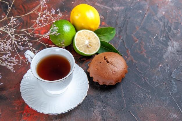 Vista ravvicinata laterale agrumi cupcakes lime limoni con foglie una tazza di tè