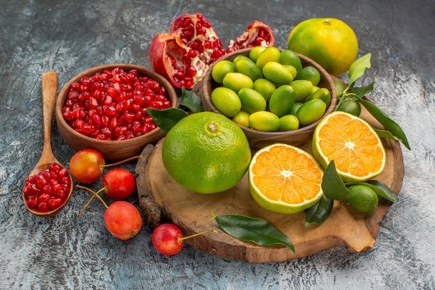 ボード上のボウルの柑橘系の果物の側面のクローズアップビューの柑橘系の果物ザクロの種子