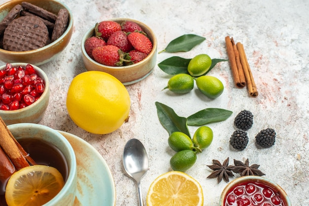 Side close-up view citrus fruits strawberries citrus fruits the appetizing cookies pomegranate lemon spoon a cup of tea with lemon and cinnamon on the table