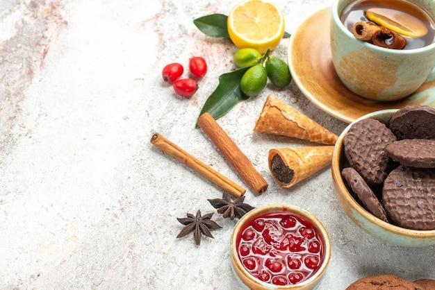 Vista ravvicinata laterale biscotti e tè al cioccolato biscotti una tazza di tè alla cannella marmellata di agrumi