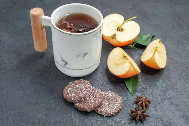 Vista ravvicinata laterale una tazza di tè fette di mela biscotti una tazza di tè con cannella