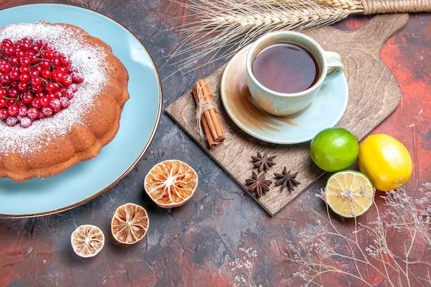 Vista ravvicinata laterale una tazza di tè una torta con frutti di bosco una tazza di tè alla cannella agrumi