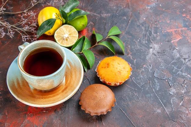 Vista ravvicinata laterale una tazza di tè una tazza di tè nero agrumi con foglie cupcakes rami