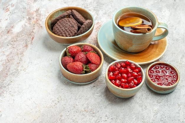 Vista ravvicinata laterale una tazza di tè una tazza di tè nero con ciotole di limone e cannella di diversi biscotti ai frutti di bosco sul tavolo
