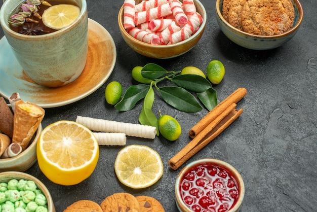 Vista ravvicinata laterale una tazza di tè una tazza di tisana al limone gli appetitosi dolci biscotti marmellata