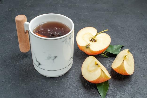 Vista ravvicinata laterale una tazza di tè una tazza di tisana con bastoncini di cannella mela sbucciata