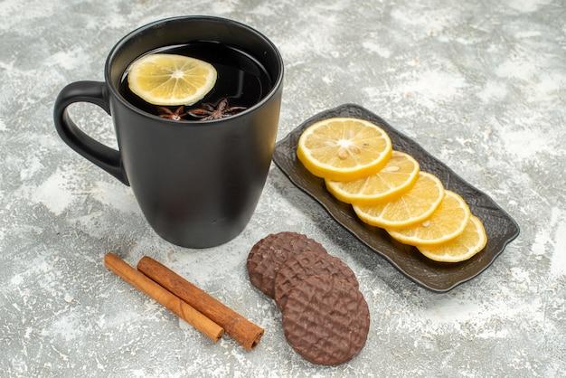 Vista ravvicinata laterale una tazza di tè una tazza di tè bastoncini di cannella biscotti fette di limone