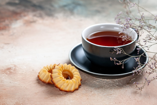 Vista ravvicinata laterale una tazza di tè una tazza di rami di albero dei biscotti del tè
