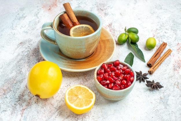 Vista ravvicinata laterale una tazza di tè una tazza di tè con limone e cannella sul piattino accanto ai semi di limone di anice stellato melograno e bastoncini di cannella sul tavolo