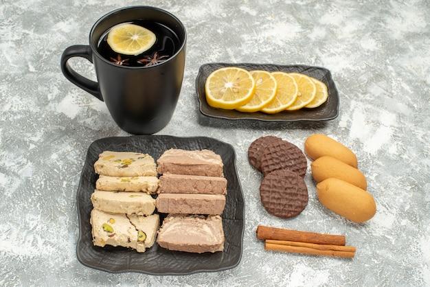 Vista ravvicinata laterale una tazza di tè una tazza di tè con una fetta di dolci al limone sulla cannella piastra