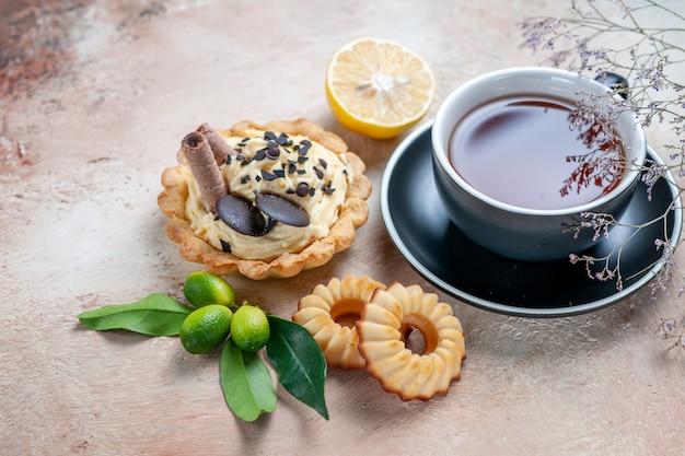 Vista ravvicinata laterale una tazza di tè cupcake una tazza di tè biscotti agli agrumi