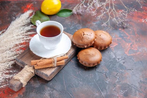 Vista ravvicinata laterale una tazza di tè cupcakes una tazza di tè cannella agrumi rami di alberi