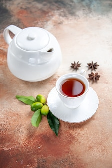 Vista ravvicinata laterale una tazza di tè bianco teiera una tazza di tè agrumi anice stellato