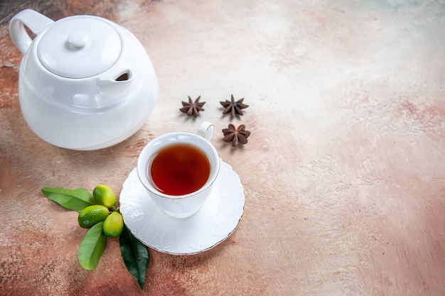 Vista ravvicinata laterale una tazza di tè bianco teiera una tazza di tè anice stellato agrumi