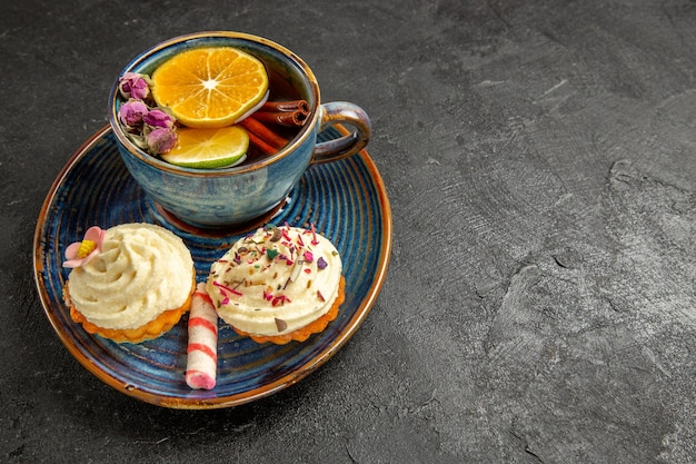 Side close-up view a cup of tea with lemon a cup of herbal tea with lemon and a saucer of cupcakes with cream and sweets on the dark table