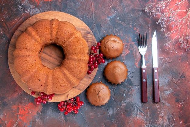 Vista ravvicinata laterale cupcakes torta cupcakes torta con ribes rosso sul tagliere forchetta coltello