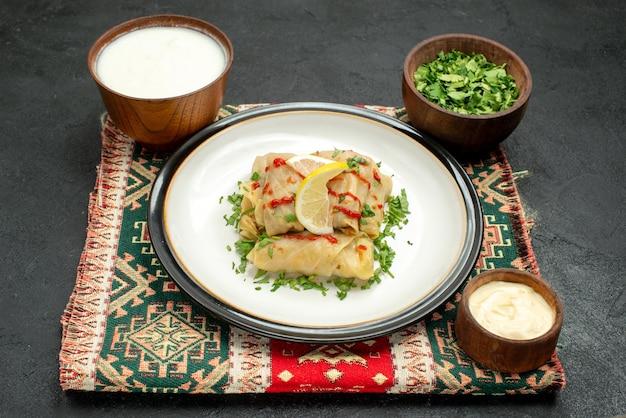 色とりどりの市松模様のテーブルクロスにキャベツを詰めたサイドクローズアップの皿とソース、テーブルの上のハーブとソースのボウル