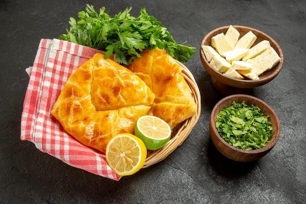 Vista ravvicinata laterale piatto in cesto ciotole di pepe nero erbe e formaggio e cesto di legno di torte erbe limone e tovaglia a scacchi sul tavolo