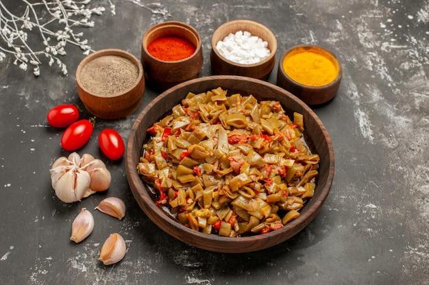 黒いテーブルの上のスパイスとニンニクのボウルの隣のプレートにトマトが入ったサヤインゲンのサイドクローズアップビューディッシュ