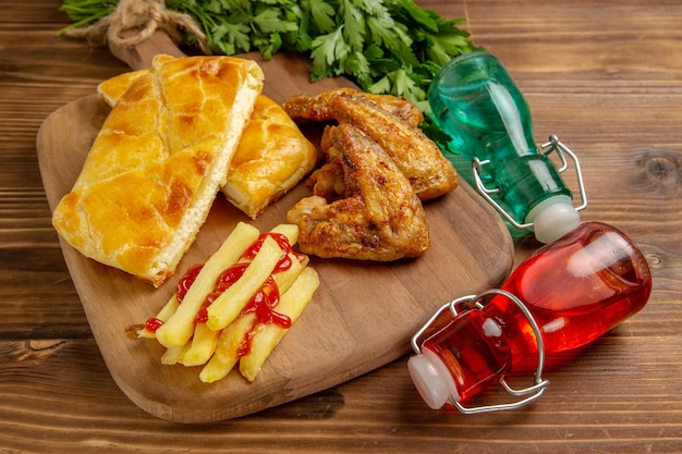 Боковой вид крупным планом блюдо на доске фаст-фуд на доске рядом с травами и красными и синими бутылками
